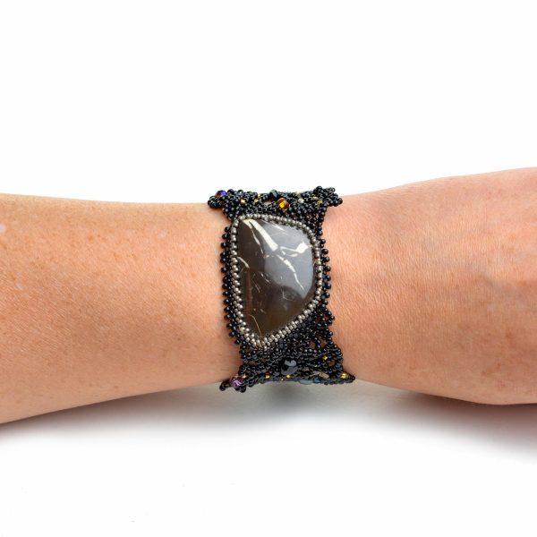 Large jasper stone in a woven beaded bracelet on a wrist of a model