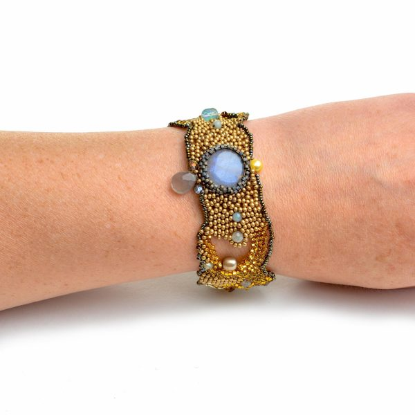 Golden woven beaded handmade bracelet with round labradorite bead on a wrist
