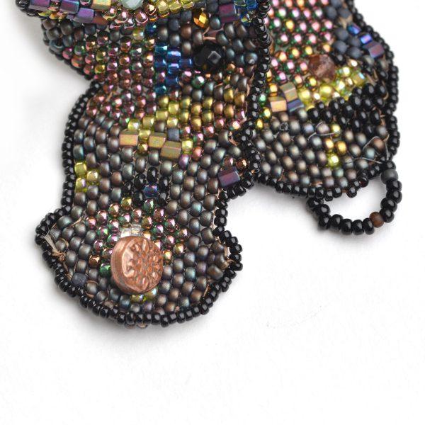 detail of handmade copper button closure on woven beaded dark gray bracelet