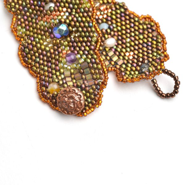 detail of copper handmade button closure on woven beaded bracelet