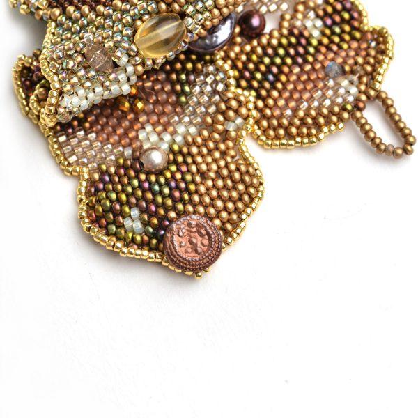 detail of copper handmade button closure of golden woven beaded bracelet