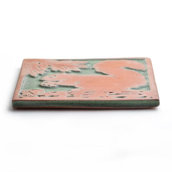 side view of Green and red square ceramic squirrel tile trivel