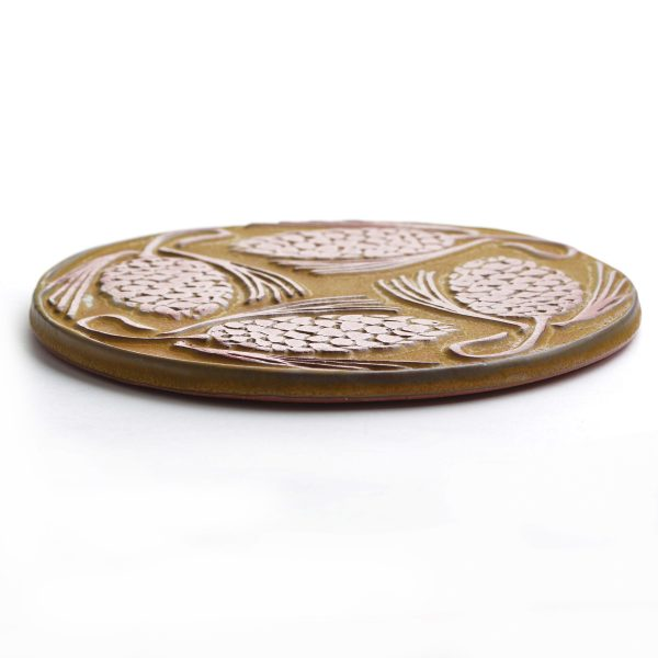 Yellow round pine cone clay trivet tile made of red clay