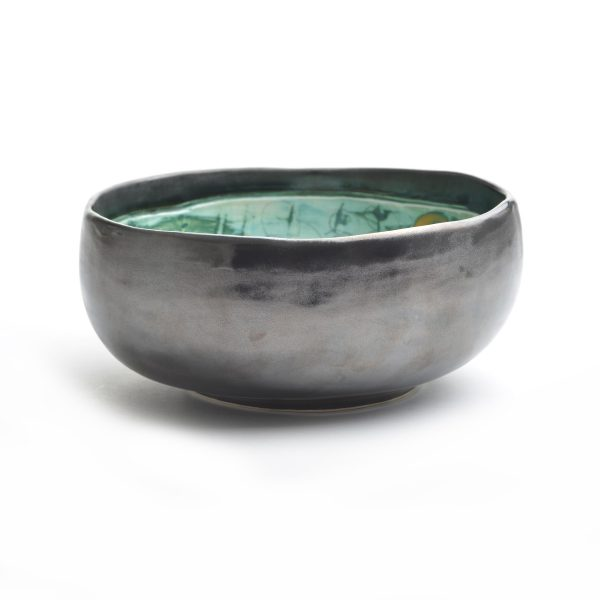 black outside of handmade ceramic bowl with green interior