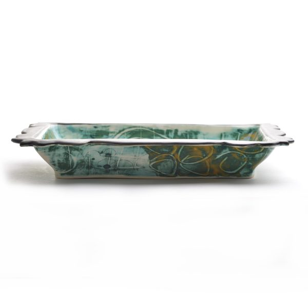 side view of handmade pottery rectangle platter with scalloped edges and green and yellow glazes