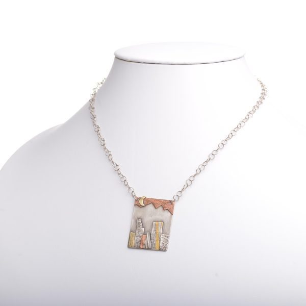 large city mountain scene mixed metal necklace with brass copper and silver and textured pieces