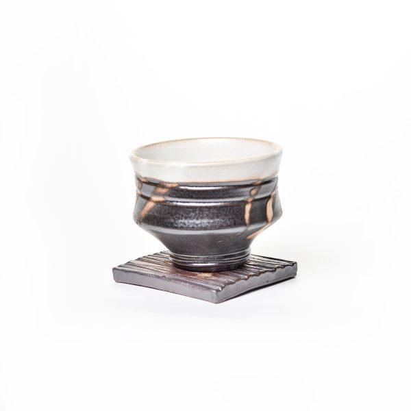 wheel thrown teabowl cup with white inside and black outside with lines, sits on flat ridged coaster