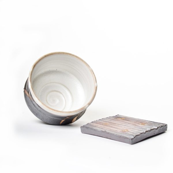 wheel thrown teabowl with white glaze inside and black porcelain, coaster with ridges, nc clay artist