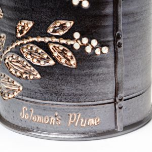 detail of wheel thrown handmade ceramic clay bucket by Sue Grier with Solomon's Plume Basket drawing of leaves, black porcelain with white glaze
