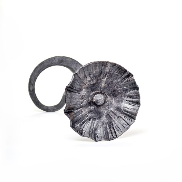 steel forged flower with patina laying on its side by Susan Hutchinson, small metal art
