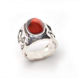 top view of handmade cast silver ring with holes in the band and spessarite garnet oval stone