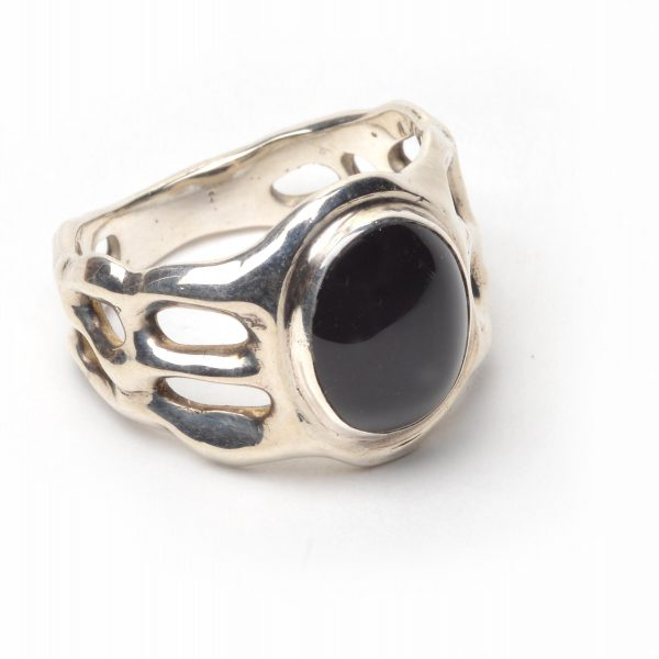 side view black onyx and silver ring, handmade ring size 8, cast silver band is organic with holes and a round black onyx stone, joseph rhodes