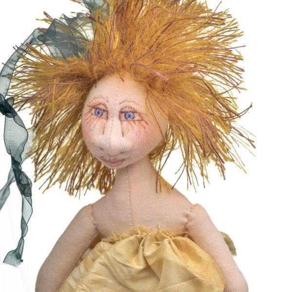detail of handmade mermaid doll with blond hair and seaweed ribbon strands, handpainted face