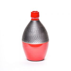 small red and black raku bottle with textured surface