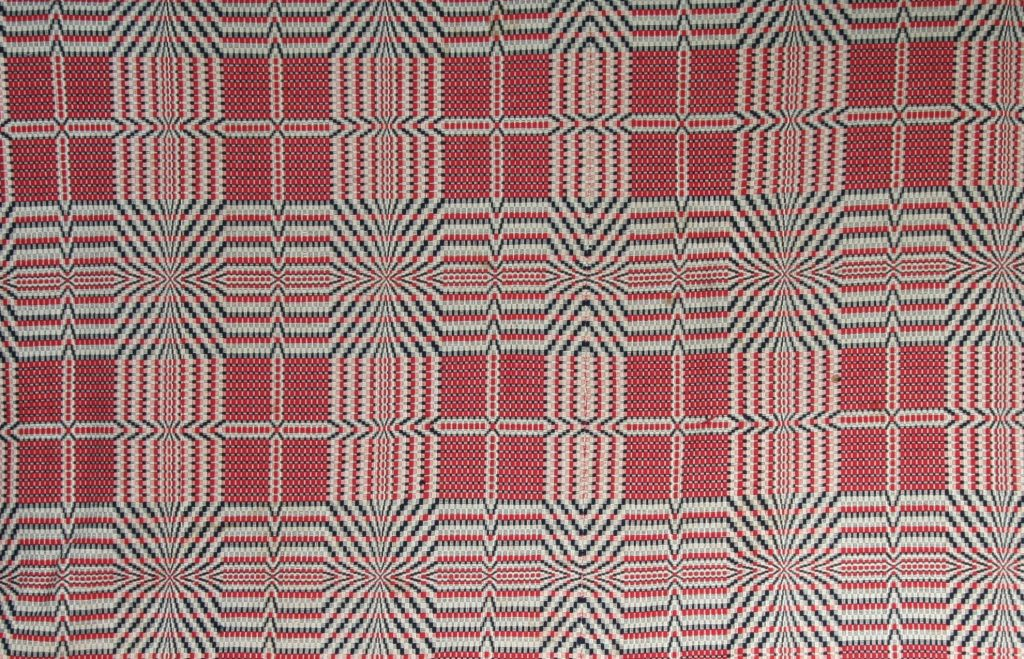 "Coverlet, c. 1900, wool and cotton - handwoven coverlet in overshot pattern. A variation of ""Sunrise"" pattern with cross center. Natural colored cotton warp. Red and blue wool weft."