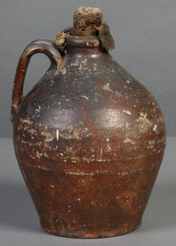 Jug with Corn Cob Stopper, stoneware - wheel thrown jug, narrow opening, applied handle at top, Corn cob stopper with bottom wrapped in cloth.