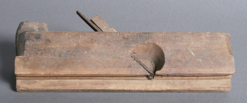 Router, c. 1850, pine - router with edge guide, two blades cut from one piece of iron, blades are different widths, handle covers blade end, handle brace at rear.