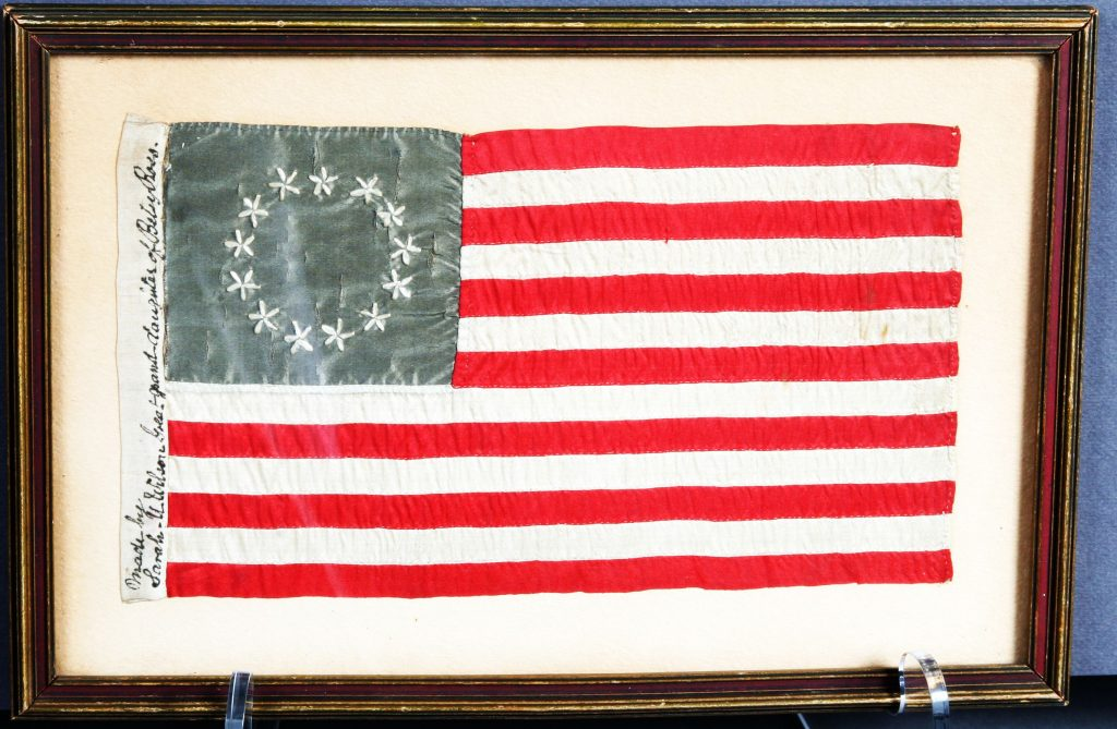 "Stars and Stripes, c. 1908, Sarah M. Wilson, A miniature copy of the first official American flag with 13 stripes of red and white. The upper left corner is a faded blue rectangle with 13 embroidered stars representing the original 13 colonies. On the back of the frame, inscribed in pencil, ""Purchased in Colonial Courthouse in Philadelphia, PA, in year 1908."" Hand sewn and embroidered. Also known as ""Gift Flag."""