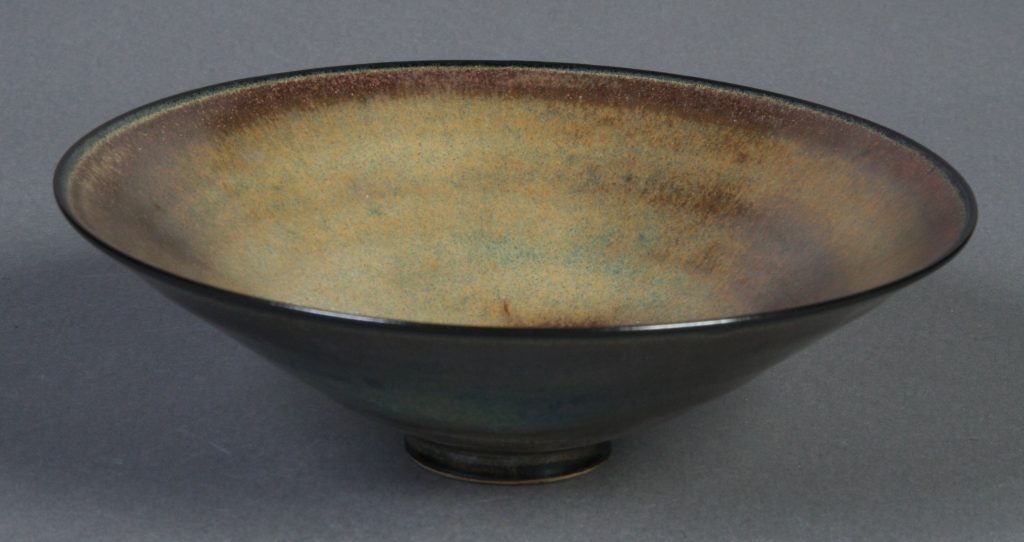 Small Footed Bowl, Edwin Schier, c. 1970, earthenware - conical shaped bowl, thin walls, small rimmed foot. Smooth glaze of browns and greens, slightly irredescent. Black along the rim, white clay body exposed on bottom of foot.