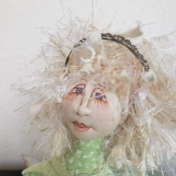 detail of handpainted fabric face on handmade pixie doll