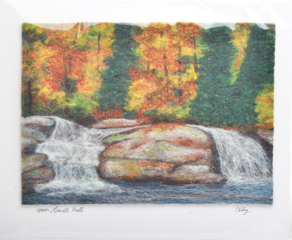 linville falls felted landscape, different colors of felt put together to form a waterfall scene mounted on a white matte