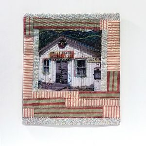 fabric image of a general store with hand embroidery and quilting details, framed fiber artwork