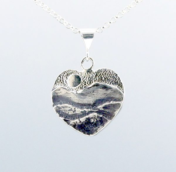 mountain necklace, heart shaped silver pendant with mountains the sun and a textured sky, hiker jewelry
