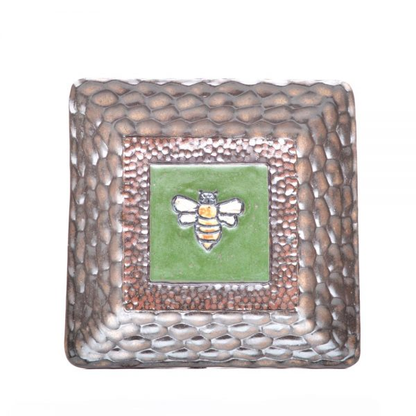 small handmade square ceramic plate with brown carved rim and a green center with a carved bee