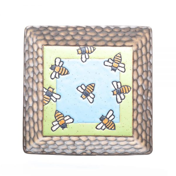 large square carved bee ceramic plate with brown rim and green and blue middle with bees carved