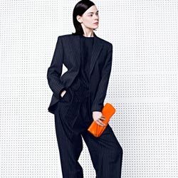 model in black with orange clutch