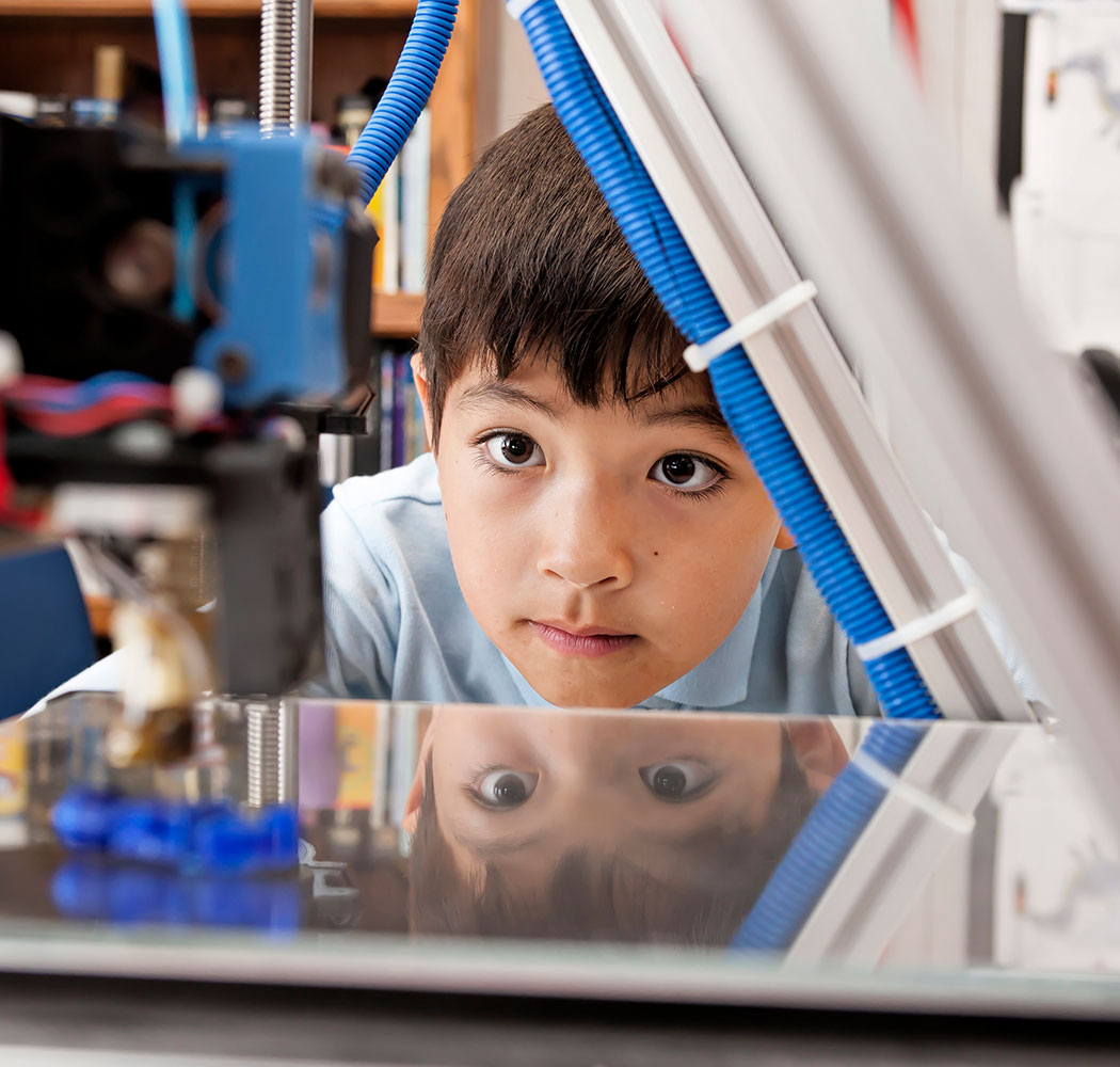 photo: young boy watching 3D printer work