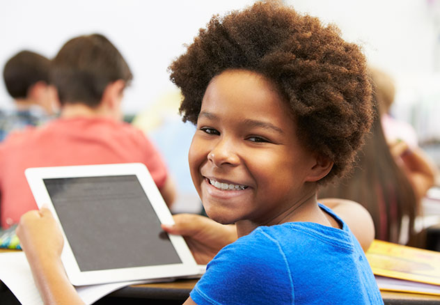 photo: young girl with afro looking over shoulder and smiling while holding a tablet