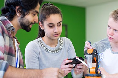 high-school boy and girl working on robotics project with male instructor