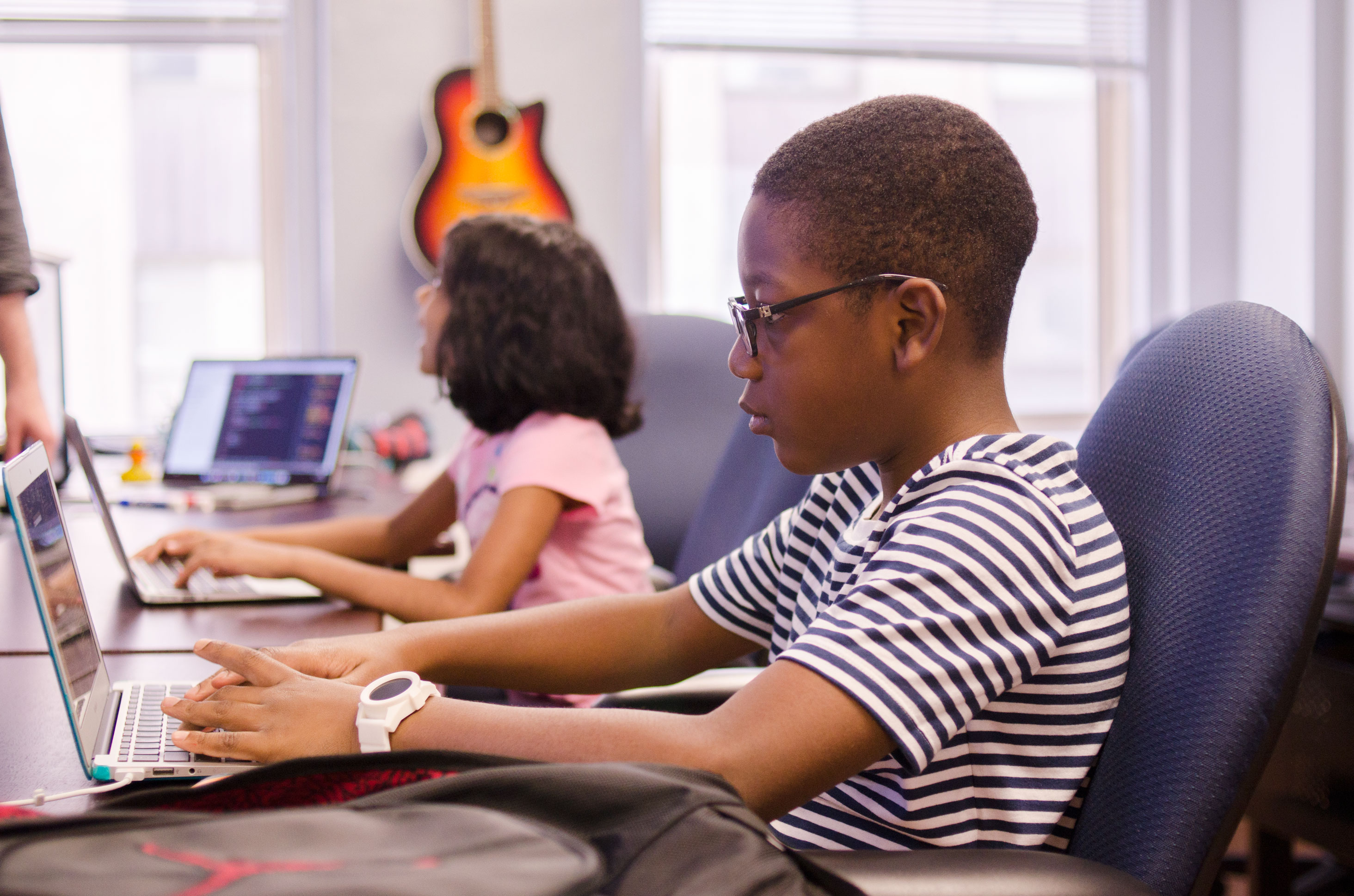 kids sharing sleek laptops at white table as teacher watches
