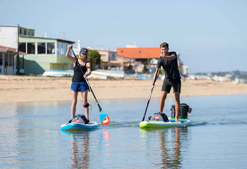 Couple paddle boarding with Red Original accessories on board