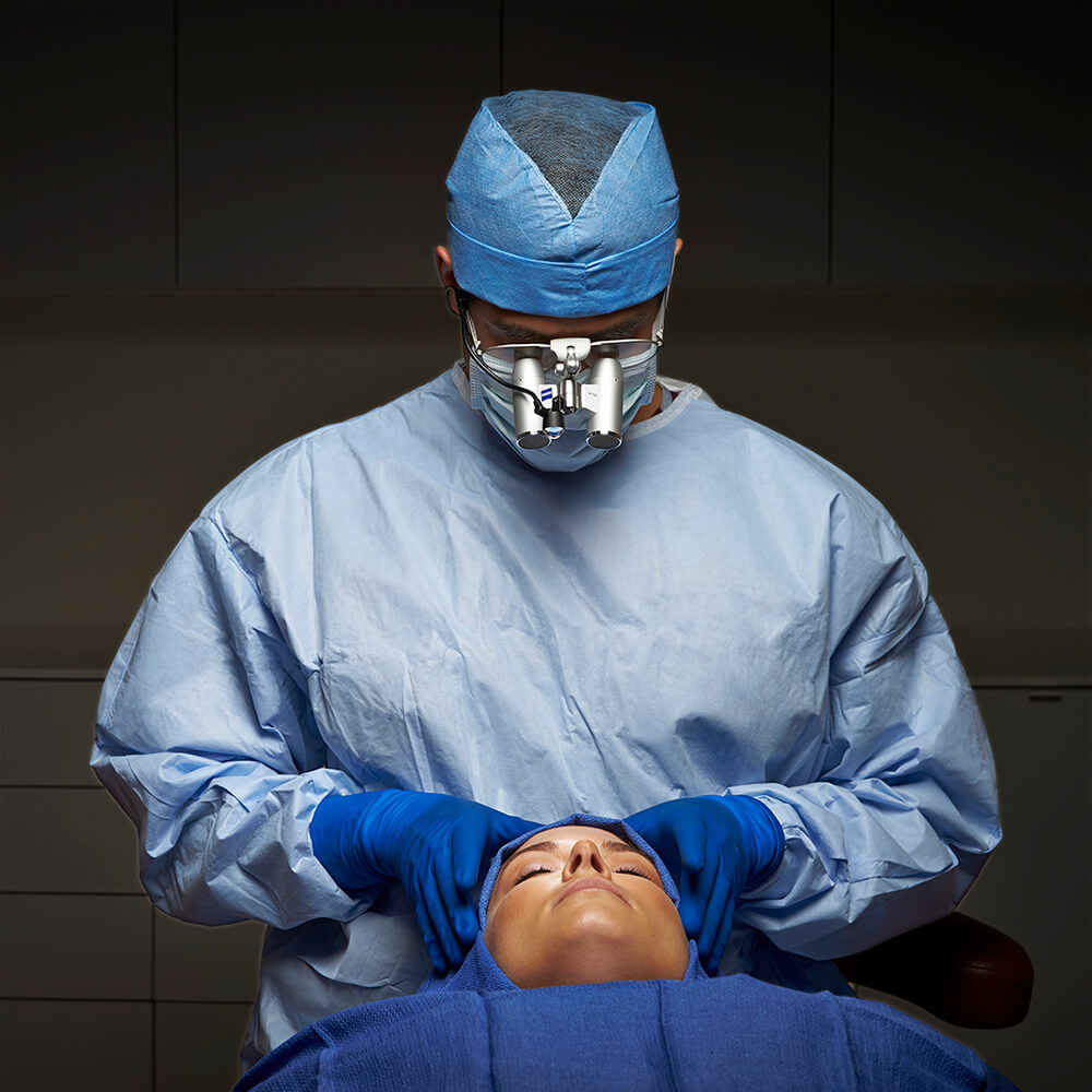 Face Aesthetics - Dr. Rad with surgical binoculars and scrubs, preparing patient for surgery