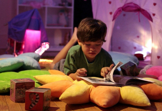 boy reading book on floor bloom pillows in reading nook