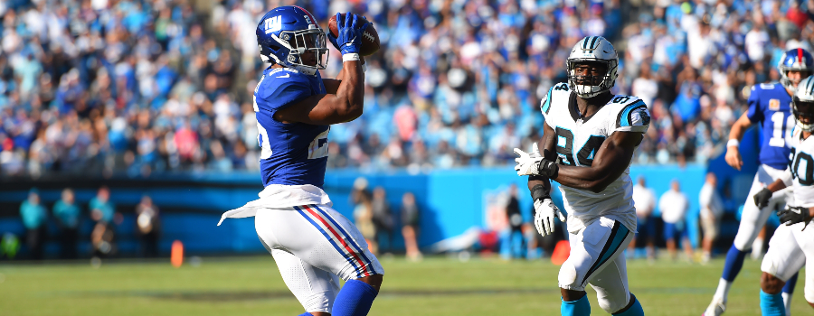 New York Giants running back Saquon Barkley (26) catches the ball and runs for a touchdown as Carolina Panthers defensive end Efe Obada (94)