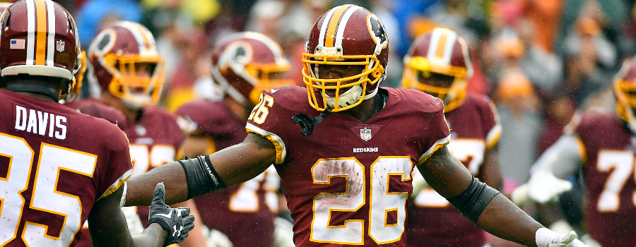 Washington Redskins running back Adrian Peterson (26) is congratulated by teammates after scoring a touchdown against the Green Bay Packers during the first half at FedEx Field.