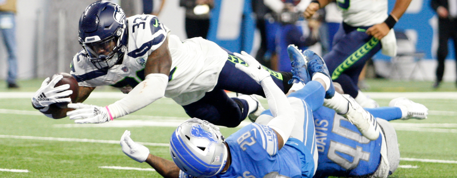 Seattle Seahawks running back Chris Carson (32) reaches for a touchdown against Detroit Lions strong safety Quandre Diggs (28) during the fourth quarter at Ford Field.