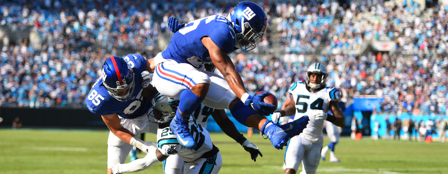 New York Giants running back Saquon Barkley (26) scores a touchdown as Carolina Panthers free safety Mike Adams (29) defends in the fourth quarter at Bank of America Stadium.