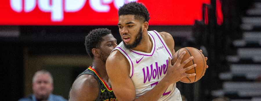 Minnesota Timberwolves center Karl-Anthony Towns (32) backs towards the basket as Atlanta Hawks guard Kent Bazemore (24) plays defense in the first half at Target Center.