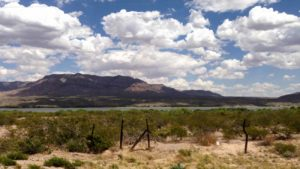 Caballo Lake with fence posts and big puffy clouds