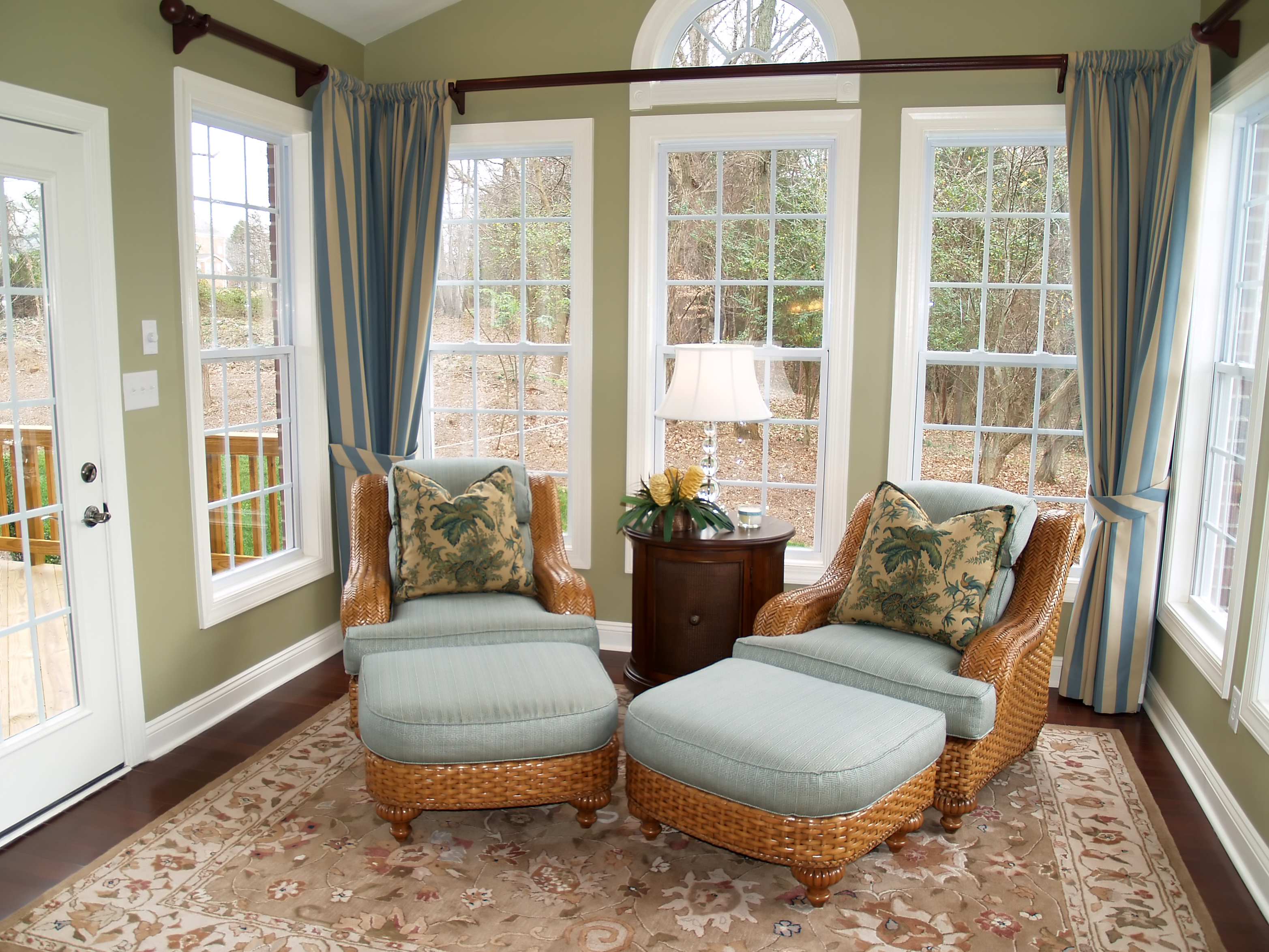 Two comfortable rattan or wicker chairs in a nicely decorated luxury sunroom