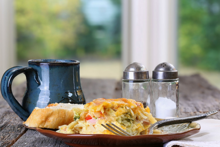 Egg, cheese, peppers, onion and sausage breakfast casserole served with coffee on a rustic table plate, fork and napkin