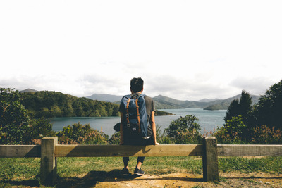 ocean, sea, water, greenery, landscape, hills, sky, clouds, tourist, backpack, sitting, fence