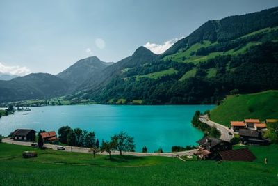 lake, water, scenery, mountain, hills, nature, greenery, village, destination, road, sky, clouds