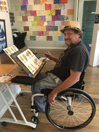 Artist Brian MacLaren in the studio at a desk painting trees for watercolor class