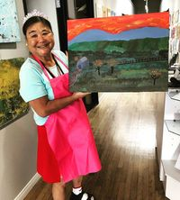 Artist Reiko Karl in a pink apron holding up a large landscape painting she created