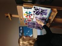 Artist Erin Ziegler in her studio standing at an easel painting